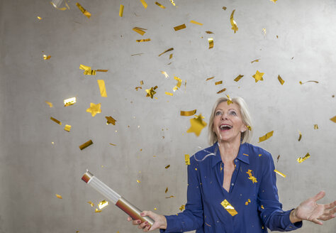 Portrait of amazed senior woman watching golden confetti - FMKF04628
