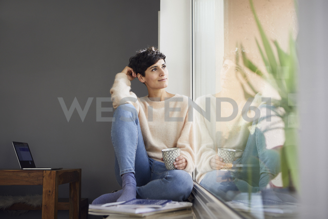 Relaxed woman at home sitting at the window - RBF06100 - Rainer Berg/Westend61
