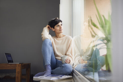 Relaxed woman at home sitting at the window - RBF06100