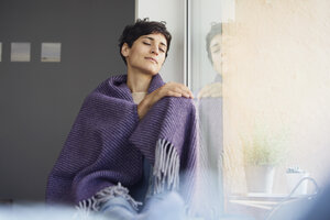 Relaxed woman at home sitting at the window - RBF06103
