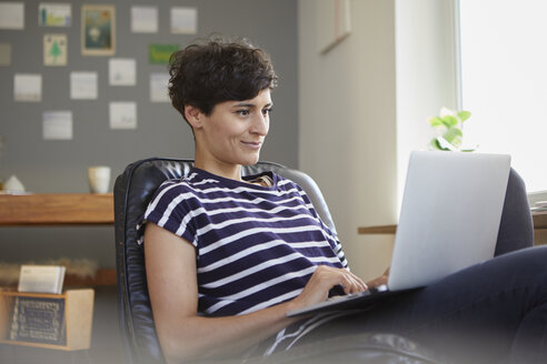 Smiling woman using laptop at home - RBF06115