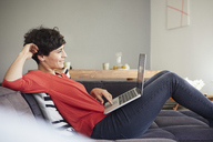 Smiling woman using laptop on couch at home - RBF06130