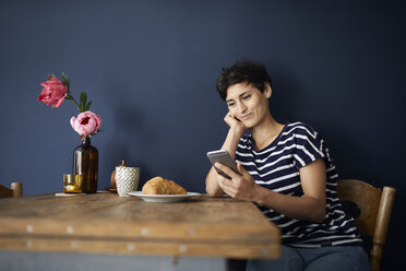 Smiling woman at home sitting at wooden table checking cell phone - RBF06142