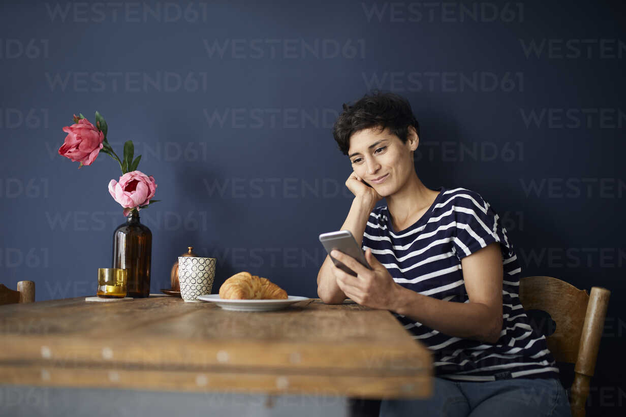 Smiling woman at home sitting at wooden table checking cell phone - RBF06142 - Rainer Berg/Westend61