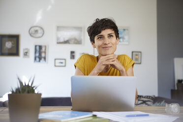 Portrait of smiling woman at home sitting at table using laptop - RBF06148
