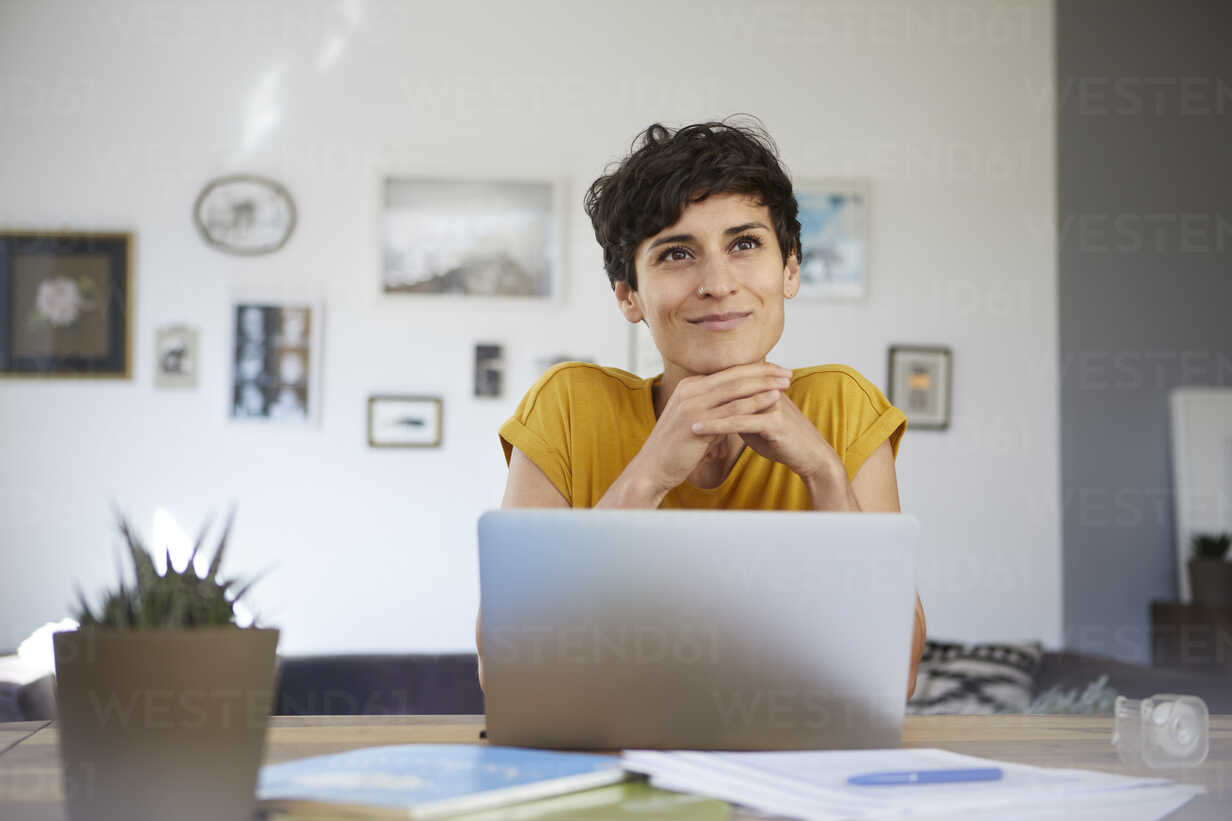Portrait of smiling woman at home sitting at table using laptop - RBF06148 - Rainer Berg/Westend61