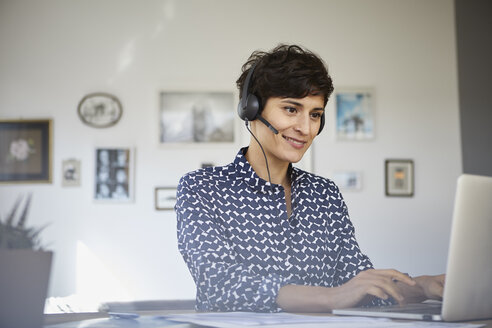 Smiling woman at home with headset using laptop - RBF06154