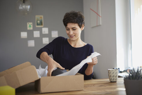 Smiling woman packing parcel at home - RBF06163