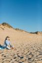 Portugal, Aveiro, woman sitting near beach dune listening music with headphones - JPF00277