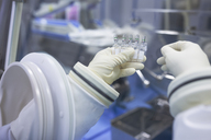 Scientist holding vials in insulator laboratory - WESTF23582