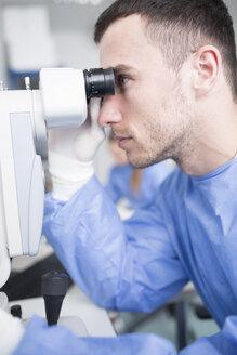 Lab technician looking through microscope - WESTF23588