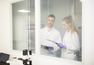 Man and woman in lab coats with clipboards behind glass pane - WESTF23642