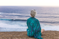 Indonesia, Lombok, woman sitting at the coast looking at view - KNTF00902