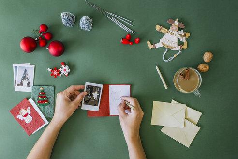 Woman's hands writing Christmas card - MOMF00291