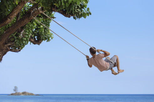 Indonesia, Lombok Island, man sitting on a swing looking at distance - KNTF00905