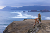 Indonesia, Lombok, woman sitting at the coast looking at view - KNTF00908