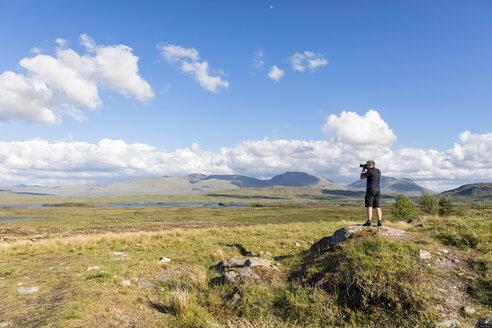 Great Britain, Scotland, Scottish Highlands, Glencoe, Rannoch Moor, Tourist photographing Loch Beinn Chaorach and Loch Ba - FOF09509