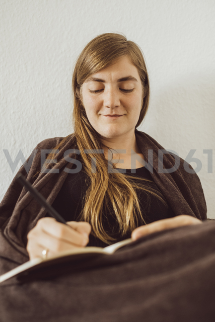 Smiling woman writing in notebook at home - JSCF00018