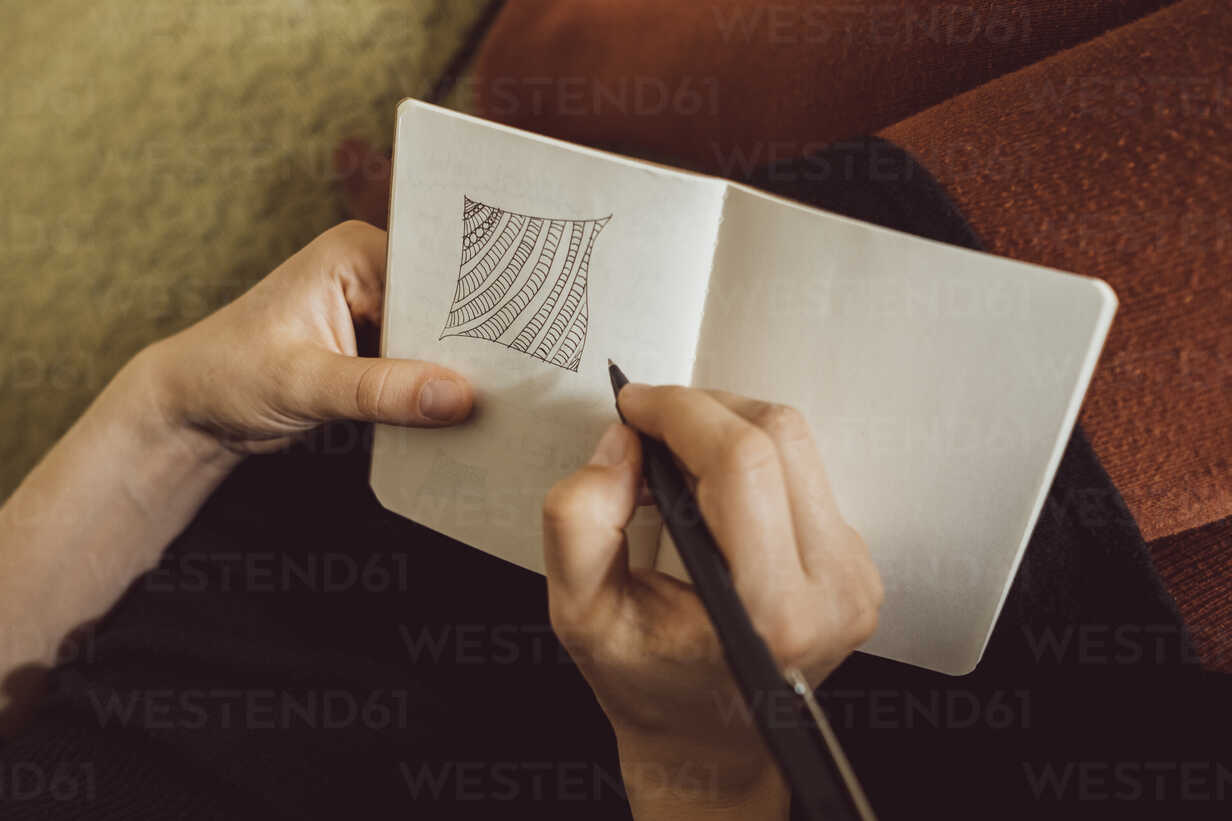 Hand of woman on couch drawing in notebook, close-up - JSCF00021 - Jonathan Schöps/Westend61