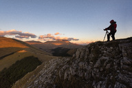 Italy, Umbria, Parco Nazionale dei Monti Sibillini, Photographer in front of Mount Vettore at sunset - LOMF00673
