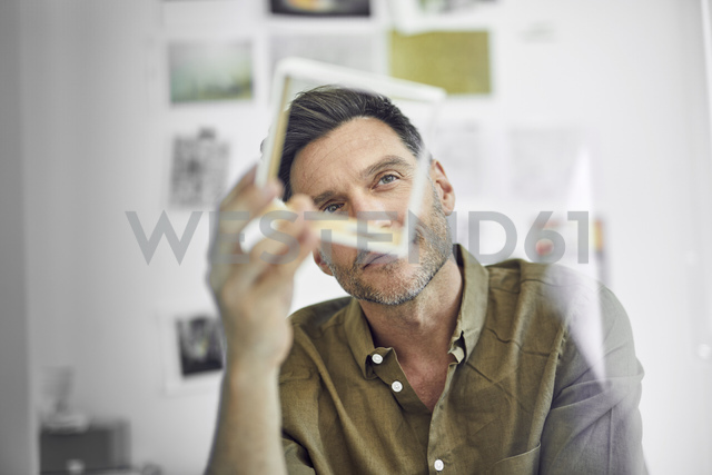 Portrait of man checking component in his office - PNEF00337