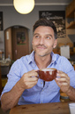 Portrait of smiling man with cup of coffee in a coffee shop - PNEF00340