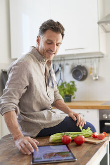 Portrait of man using tablet in the kitchen - PNEF00346