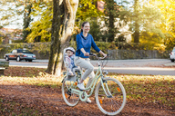 Mother and daughter riding bicycle, baby wearing helmet sitting in children's seat - DIGF03172