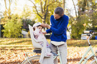 Mother and daughter riding bicycle, baby wearing helmet sitting in children's seat - DIGF03178