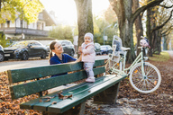 Mother and daughter taking a break on a park bench - DIGF03181