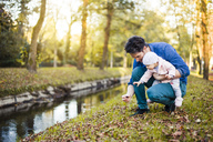Father searching for chestnuts in park, with baby daughter on his lap - DIGF03184