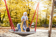 Happy baby girl relaxing with her mother on a swing in autumn - DIGF03191