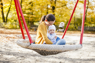 Happy baby girl relaxing with her mother on a swing in autumn - DIGF03194