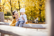 Happy baby girl and her mother having fun on a playground in autumn - DIGF03203