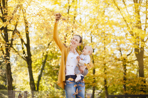 Mother and baby girl having fun with leaves in autumn - DIGF03206