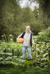 Portrait of smiling young woman with spade and pumpkin in garden - JOSF01882