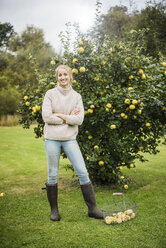 Portrait of smiling young woman at quince tree in garden - JOSF01885