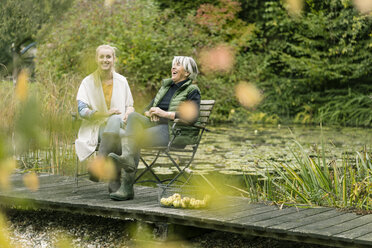 Happy young woman with her grandmother sitting on jetty at garden pond - JOSF01891