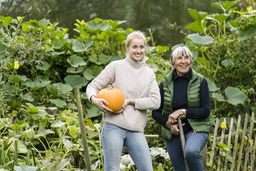 Happy young woman with her grandmother holding pumpkin in garden - JOSF01894