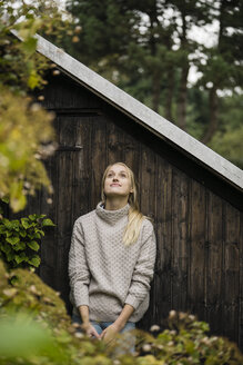 Smiling young woman at garden shed in garden - JOSF01900