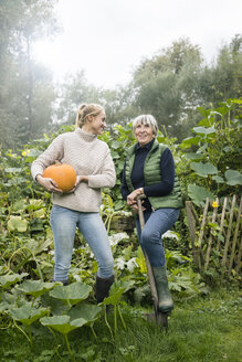 Happy young woman with her grandmother holding pumpkin in garden - JOSF01906