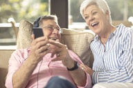 Happy senior couple with cell phone and headphones on couch at home - ZEF14728