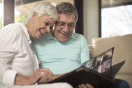 Happy senior couple sitting on couch looking at photo album - ZEF14737