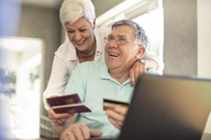 Happy senior couple holding passports booking their trip together online - ZEF14746