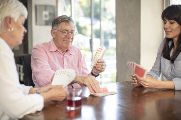 Senior couple playing cards with daughter at home - ZEF14761