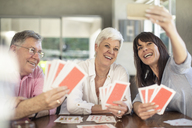 Happy senior couple playing cards and taking a selfie with daughter at home - ZEF14764