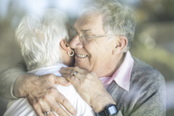 Happy senior couple hugging behind windowpane - ZEF14767