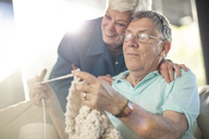 Happy senior couple on couch at home knitting - ZEF14776
