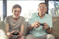 Grandfather and grandson playing video game on couch at home - ZEF14779