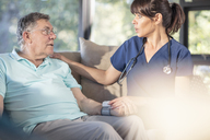 Nurse caring for of senior patient at home - ZEF14782